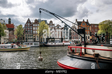 Amsterdam, Netherlands - 27 April, 2017: Cruise tourist boat against Houseboats, living barges and typical curves dutch houses with large windows in B - Stock Photo