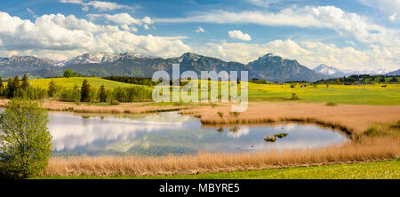 panoramic landscape in Bavaria with alps mountain range and lake - Stock Photo