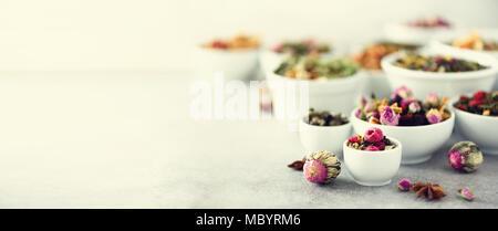 Assortment of dry tea in white bowls. Tea backgound: green, black, floral, herbal, mint, melissa, ginger, apple, rose, lime tree, fruits, orange, hibiscus, raspberry, cornflower, cranberry. Banner - Stock Photo