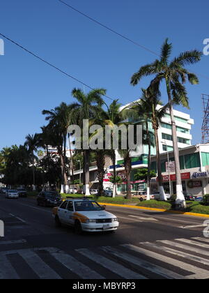 ACAPULCO, MEXICO NORTH AMERICA on MARCH 2018: White buildings, pedestrian crossing, cars on scenic street with exotic palms trees in mexican city with - Stock Photo