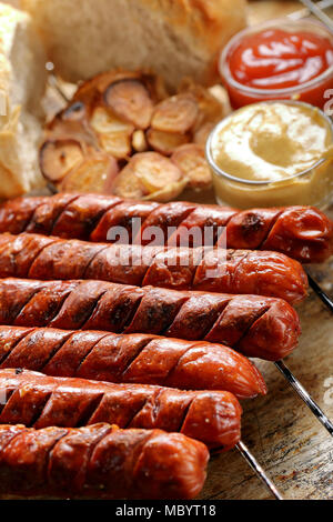 Grilled sausages with sauce ketchup and mustard on metal grate - Stock Photo