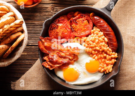 English Breakfast with sausages, grilled tomatoes, egg, bacon, beans and bread on frying pan. - Stock Photo