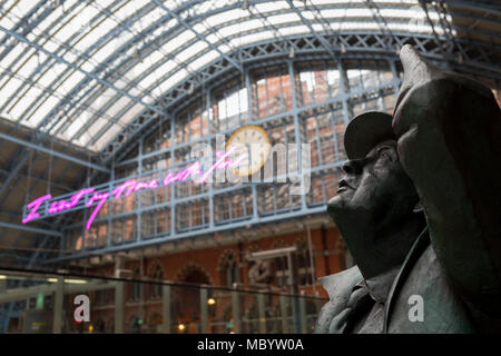 The statue of poet John Betjeman by Martin Jennings looks up to the new artwork entitled 'I Want My Time With You' by British (Britpop) artist Tracy Emin which hangs over the main concourse at St. Pancras Station, on 10th April 2018, in London, England. In the sixth year of the Terrace Wires Commission - and in celebration of the 150th anniversary of St Pancras International and the 250th anniversary of the Royal Academy of Arts, at one of London's mainline station, the London hub for Eurostar - the 20 metre-long greeting to commuters reads 'I Want My Time With You' and Emin thinks that arrivi - Stock Photo