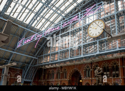 The new artwork entitled 'I Want My Time With You' by British (Britpop) artist Tracy Emin hangs over the main concourse at St. Pancras Station, on 10th April 2018, in London, England. In the sixth year of the Terrace Wires Commission - and in celebration of the 150th anniversary of St Pancras International and the 250th anniversary of the Royal Academy of Arts, at one of London's mainline station, the London hub for Eurostar - the 20 metre-long greeting to commuters reads 'I Want My Time With You' and Emin thinks that arriving by train and being met by a lover as they put their arms around the - Stock Photo