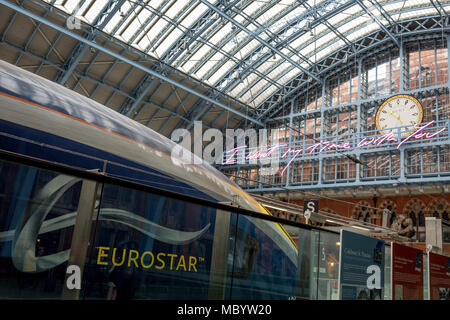 A Eurostar train and the new artwork entitled 'I Want My Time With You' by British (Britpop) artist Tracy Emin hangs over the main concourse at St. Pancras Station, on 10th April 2018, in London, England. In the sixth year of the Terrace Wires Commission - and in celebration of the 150th anniversary of St Pancras International and the 250th anniversary of the Royal Academy of Arts, at one of London's mainline station, the London hub for Eurostar - the 20 metre-long greeting to commuters reads 'I Want My Time With You' and Emin thinks that arriving by train and being met by a lover as they put  - Stock Photo