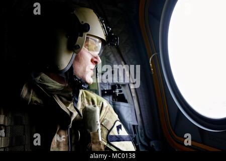 Sgt. Shane Outlaw, a CH-47 Chinook helicopter crewmember assigned to Company B, 2nd General Support Aviation Battalion, 227th Aviation Regiment, 1st Combat Aviation Brigade, 1st Cavalry Division, looks out over the Hohenfels Training Area in Germany during a local area orientation flight, Jan 16, 2018. Aviators of the battalion are familiarizing themselves with the training area to be prepared for the support they will provide during the upcoming Allied Spirit VIII exercise. (U.S. Army photo by Sgt. Gregory T. Summers / 22nd Mobile Public Affairs Detachment) - Stock Photo