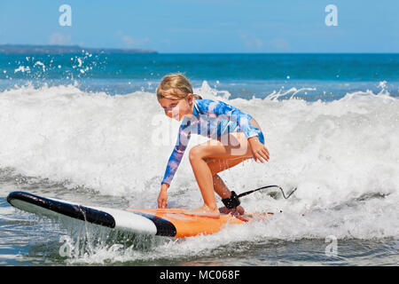 Happy baby girl - young surfer ride on surfboard with fun on sea wave Active family lifestyle, kids outdoor water sport lessons and beach activities