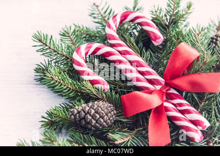 Close up of a fir tree and candy cones tied with a red bow over an old white wood background. Christmas decoration background. - Stock Photo