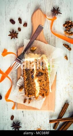 Top view of a homemade carrot cake with raisins, walnuts and cinnamon over white wooden background. Cream cheese frosting. - Stock Photo