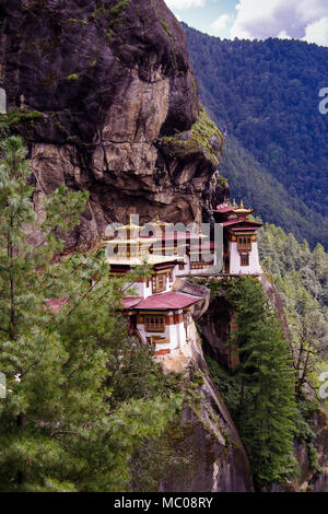 Taktsang Palphug Monastery or Tiger's Nest: Red and gold rooftops, perched on cliffside of the upper Paro valley, Bhutan - Stock Photo