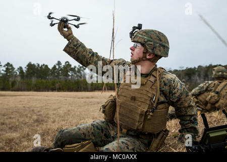 U.S. Marine Lance Cpl. James R. Fiers, Jr., a rifleman with Battalion Landing Team, 2nd Battalion, 6th Marine Regiment, 26th Marine Expeditionary Unit (MEU), releases a drone during a live-fire platoon attack on Camp Lejeune, N.C., Jan. 17, 2018. The training was held to improve leadership development, fire and maneuverability skills, and marksmanship for an upcoming deployment. (U.S. Marine Corps photo by Lance Cpl. Tojyea G. Matally) - Stock Photo