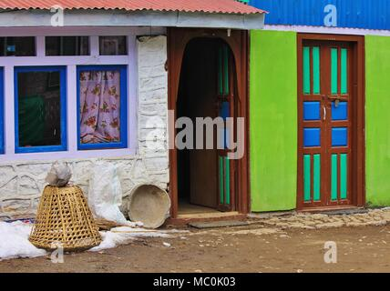 Colorful painted doors and facade. Braided basked used for transporting goods. Scene in Nepal.