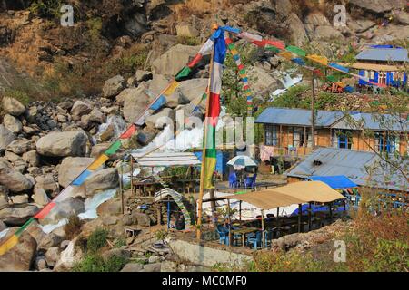 Scene on the way to Langtang, Nepal. River and small huts. Multi colored prayer flags. - Stock Photo