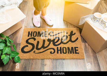 Woman in Pink Shoes and Sweats Standing Near Home Sweet Home Welcome Mat, Boxes and Plant. - Stock Photo