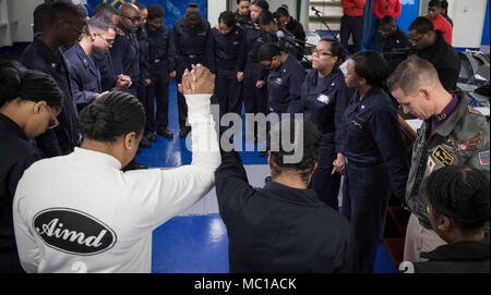 ATLANTIC OCEAN (Jan. 21, 2018) -- Sailors assigned to USS Gerald R. Ford (CVN 78) gather in prayer following the ship's first gospel service held in the forecastle. Ford is underway conducting test and evaluation operations. (U.S. Navy photo by Mass Communication Specialist 3rd Class Connor D. Loessin) - Stock Photo