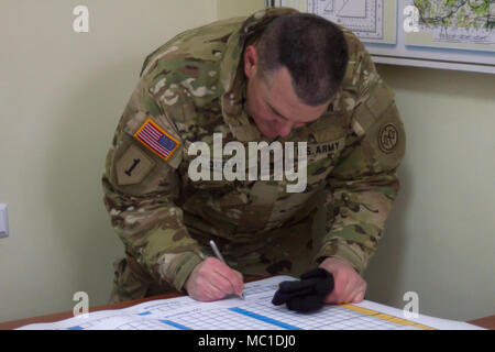 Yavoriv, Ukraine – Col. Dennis Deeley, the 27th Infantry Brigade Combat Team (forward) commander, signs training documents following an rotational unit opening ceremony here Jan. 22. During the next two months, more than 200 New York Army National Guard Soldiers stationed in Ukraine will help train and mentor the Ukrainian Army's 3rd Battalion of the 14th Mechanized Brigade as it pursues its goal of achieving NATO interoperability. (U.S. Army photo by Sgt. Alexander Rector) - Stock Photo