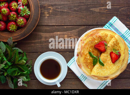 Pile of golden pancakes with strawberries and strawberry jam, decorative sprig of mint. The top view - Stock Photo