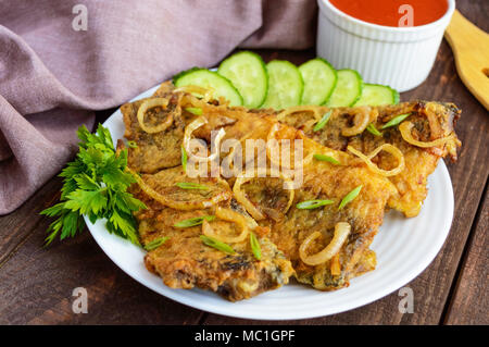Fried carp fish fillet in batter on wooden table - Stock Photo