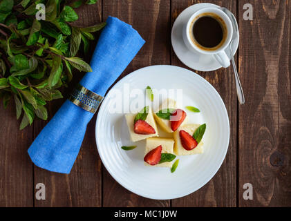 Delicate cottage cheese and creamy souffle in the form of cubes, decorating with mint leaves and fresh strawberries on a white plate - Stock Photo