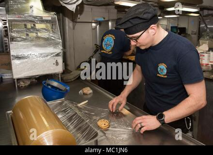 180122-N-OX360-003 PORTSMOUTH, Va. (Jan. 22, 2018) Culinary Specialist 3rd Class David Ackley, from Port Ricky, Fla, wraps cookies aboard the aircraft carrier USS Dwight D. Eisenhower (CVN 69)(Ike). Ike is undergoing a Planned Incremental Availability (PIA) at Norfolk Naval Shipyard during the maintenance phase of the Optimized Fleet Response Plan (OFRP). (U.S. Navy photo by Mass Communication Specialist Seaman James Norket) - Stock Photo