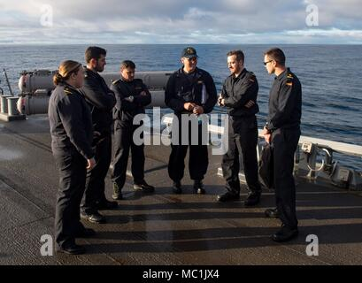 ATLANTIC OCEAN (Jan. 21, 2018) Lt. Robert Harris, middle, the plans and tactics officer aboard the Arleigh Burke-class guided-missile destroyer USS Ross (DDG 71), gives a tour to liaison representatives from the Spanish navy during an exercise between the United States and Spain Jan. 21, 2018. Ross is currently participating in an at-sea exercise with the Spanish navy designed to improve the countries' interoperability when conducting maritime training, including gun and small-boat evolutions. Ross, forward-deployed to Rota, Spain, is on its sixth patrol in the U.S. 6th Fleet area of operation - Stock Photo