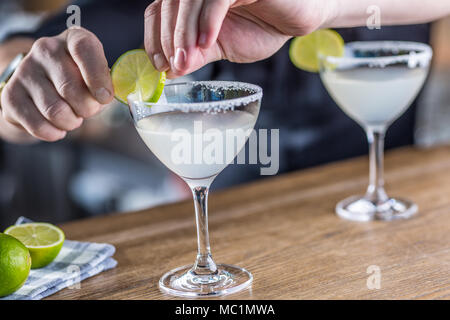 Barman in pub or restaurant  preparing a cocktail drink margarita. - Stock Photo