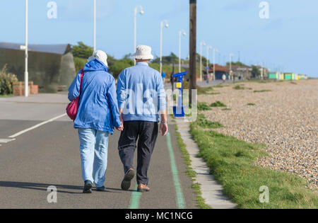 Senior couple walking away holding hands along the seafront promenade, on a sunny day in Littlehampton, West Sussex, England, UK. seafront stroll. - Stock Photo