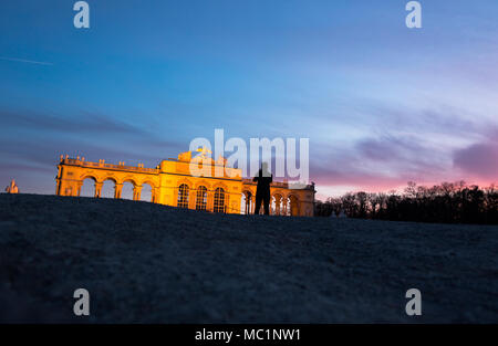 Gloriette in Schönbrunner Schloss Park at late evening in golden hour light. Low, wide angle perspective, shoot from ground level. Tourist making a ph - Stock Photo
