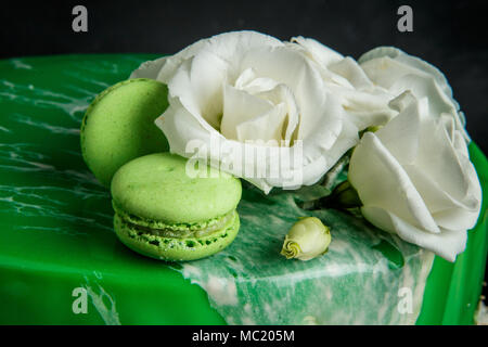closeup topping of glazed green cake decorated with  white flowers and macaroons - Stock Photo