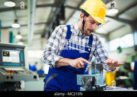Metal industry factory worker working on metal parts - Stock Photo