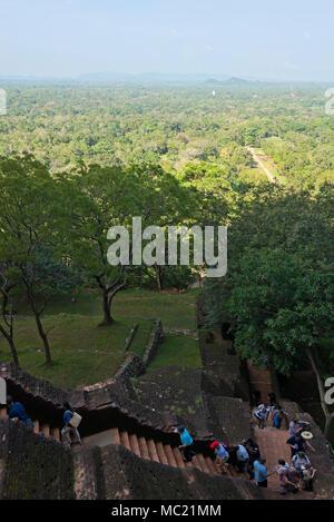 Vertical view of tourists beginning the walk up Sigiriya or Lions Rock in Sri Lanka. - Stock Photo