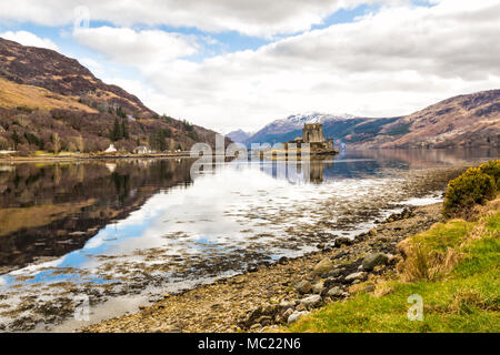 Eilean Donan Castle reflected in Loch Long at high tide, Dornie, Western Highlands, Scotland, UK in March - Stock Photo