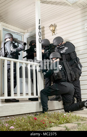 Police tactical or swat team gathered round the door of a house with drawn weapons and protective clothing simulating an arrest or hostage stand-off s - Stock Photo