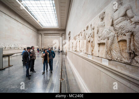 London. England. Visitors to the British Museum looking at the ancient Parthenon Frieze (Elgin Marbles), in the Duveen Gallery, from the Parthenon on  - Stock Photo