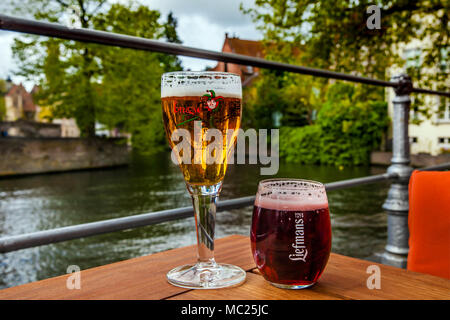 Two glasses of belgian beer standing on the table with the city view - Stock Photo