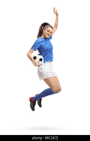 Full length portrait of a female soccer player jumping and gesturing happiness isolated on white background - Stock Photo