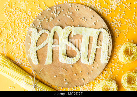 The word pasta is laid out in voluminous letters from small raw macaroni on a wooden round board among various types of pasta. Food on a bright backgr - Stock Photo
