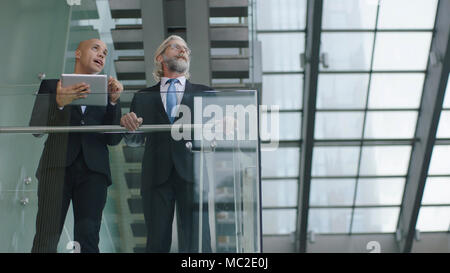 two design professionals standing in modern glass and steel building having a discussion using digital tablet. - Stock Photo