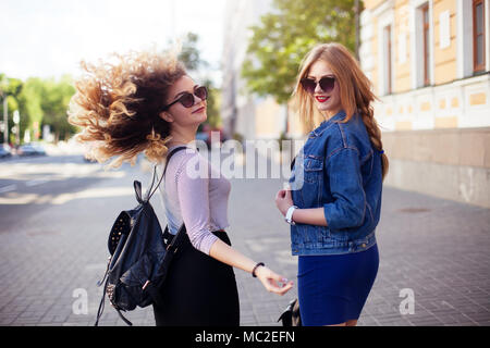 Outdoor lifestyle portrait of two best friends, smiling and having fun together, enjoy each other company posing to camera - Stock Photo