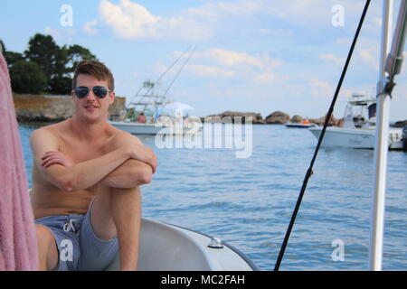 A man with sunglasses and blue stripped shorts on a boat in Rockport. Summer relaxing with friends and boats in the background. - Stock Photo