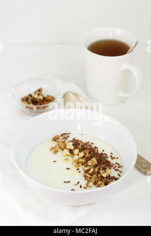 Traditional semolina porridge with butter, nuts and flax seed. A useful breakfast of porridge and tea. Rustic style. - Stock Photo