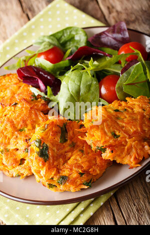 Fried pancakes from sweet potato and fresh mix salad on a plate close-up. vertical - Stock Photo