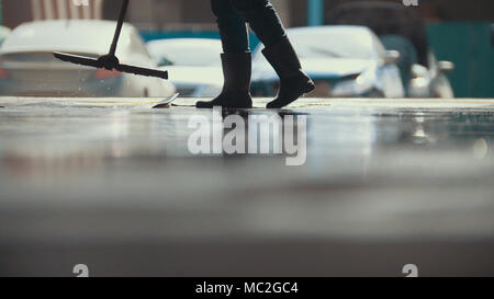 Worker remove foam and water with a MOP after car washing - Stock Photo