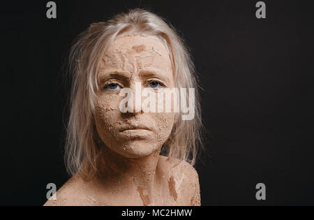 disheveled woman covered in dry cracked mud with copy space - Stock Photo