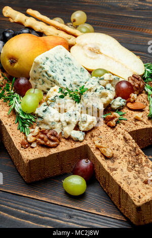 pears and cheese on wooden cutting board - Stock Photo