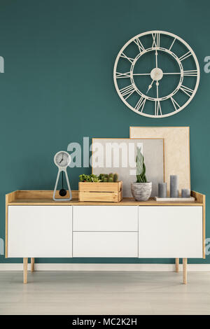 Gold round clock on green wall above white cupboard with posters and plant in living room interior - Stock Photo