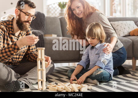 Young parents playing with wooden blocks with their son in a living room