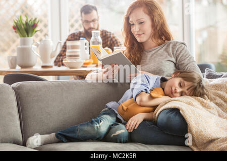 Sleeping son lying on mother's lap while she is reading a book and father eating in the background - Stock Photo