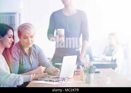 Two women sitting in an office with laptop and man standing next to them - Stock Photo