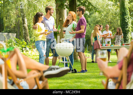 Group of young friends talking on sunny day, enjoying summer holidays drinking beer and having barbecue party in nature - Stock Photo